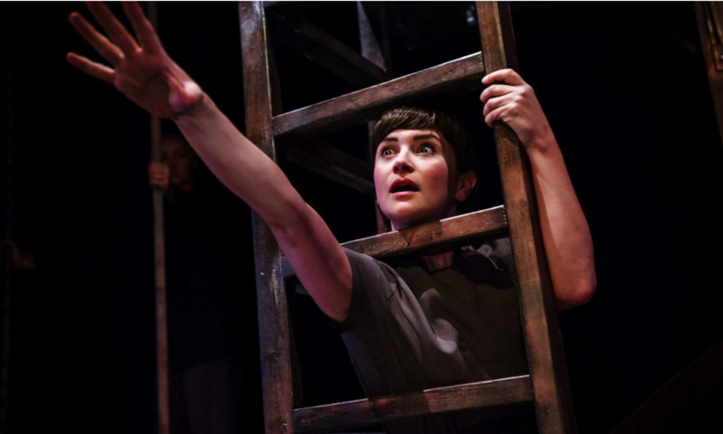 Holly Georgia (Antigone) stretches out her hand on a ladder in Antigone from Actors of Dionysus (c) Alex Brenner