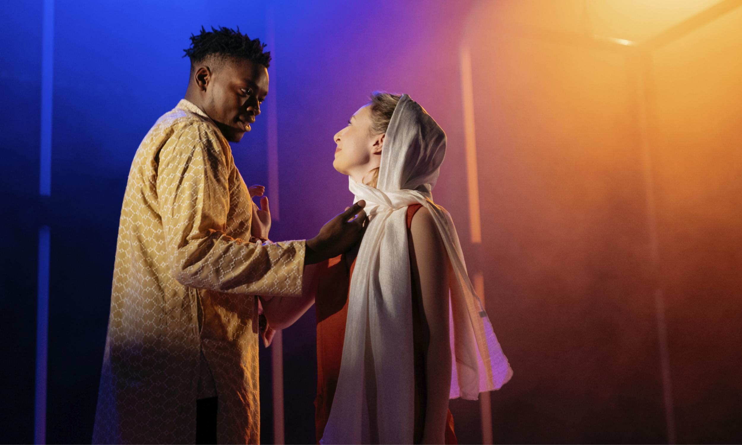 Victor Oshin (Othello) reaches towards Kitty Archer (Desdemona) as they look into each other's eyes. From ETT's Othello © Helen Murray.